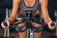 Stationary bicycles fitness girl in a gym sport club. Sport young woman on a stationary bike in the gym Royalty Free Stock Image