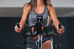 Stationary bicycles fitness girl in a gym sport club. Royalty Free Stock Image