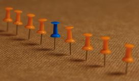 Stationary, Blue Pushpin in Row with Orange, Concept for Difference, Individuality, Leadership. Down grade. Copy Space. Stationary, Blue Pushpin in Row with Stock Images