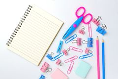 Stationary concept, Flat Lay top view Photo of Scissors, pencils. Paper clips, sticky note,staple with blank note pad in pink and blue tone on white background Stock Photography
