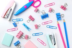 Stationary concept, Flat Lay top view Photo of Scissors, pencils. Paper clips, post it,stapler in pink and blue tone on white background with copy space Royalty Free Stock Images