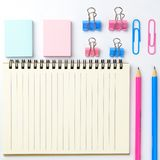 Stationary concept, Flat Lay top view Photo of Scissors, pencils. Paper clips, sticky note,staple with blank note pad in pink and blue tone on white background Royalty Free Stock Photography