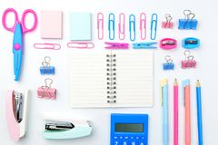 Stationary concept, Flat Lay top view Photo of Scissors, pencils. Paper clips, sticky note,staple with blank note pad in pink and blue tone on white background Stock Photos
