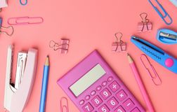 Stationary concept, Flat Lay top view Photo of Scissors, pencils. Paper clips,calculator,sticky note,stapler and notepad in pink and blue tone on pink Stock Image