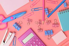 Stationary concept, Flat Lay top view Photo of Scissors, pencils. Paper clips,calculator,sticky note,stapler and notepad in pink and blue tone on pink Royalty Free Stock Photo