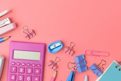 Stationary concept, Flat Lay top view Photo of Scissors, pencils. Paper clips,calculator,sticky note,stapler and notepad in pink and blue tone on pink Stock Images