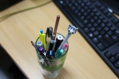 Stationary glass that contain a lot of pens and pencils. Stationary glass that contain a lot of pens and pencils with blur keyboard background Royalty Free Stock Image