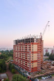 Stationary hoist and brick tall building under construction Royalty Free Stock Image