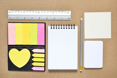 Stationary objects. Note paper post it with stationary objects on brown background Royalty Free Stock Photos