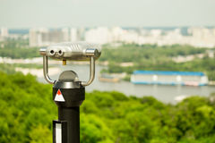 Stationary observation binoculars , metropolis landscape on the background with bridge, river, boats,  subway, and skyscrapers Stock Photo