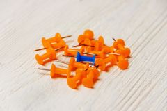Stationary, Orange, Blue Pushpins Heap on White Wooden Background, Concept for Difference, Individuality. Stationary, Orange, Blue Pushpins Heap on White Wooden Stock Photo