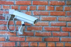 Stationary outdoor video camera of a security video surveillance system on a brick wall stock image