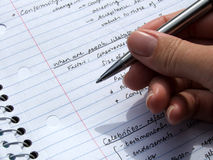 Stationary - Pen held in hand. Pen is held over writings in an open notebook royalty free stock photography