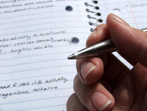 Stationary - Pen held in hand. Pen is held over writings in an open notebook royalty free stock photos