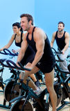 Stationary spinning bicycles fitness  group. Stationary spinning bicycles fitness men in a gym sport club Royalty Free Stock Photography
