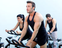 Stationary spinning bicycles fitness group. Stationary spinning bicycles fitness men in a gym sport club Stock Image