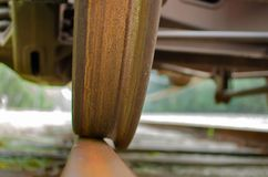 Old train of a rusty wheel riding on a shiny steel rail Royalty Free Stock Image