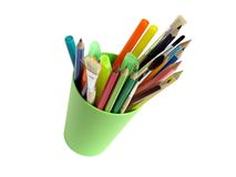 Stationery. Pencils,brushes and soft-tip pens in a green plastic glass Stock Photos