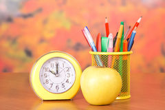 Stationery, alarm clock and apple Stock Images