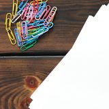 Stationery clips and paper on wooden background royalty free stock photos