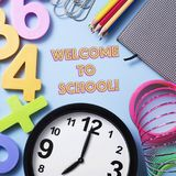 Stationery, clock and text welcome to school. Closeup of a clock, some pencil crayon of different colors, a notepad, some paper clips, some numbers of different Royalty Free Stock Photography