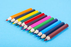 Stationery: colored pencils on blue background. Royalty Free Stock Photos