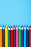 Stationery: colored pencils on blue background. Royalty Free Stock Images