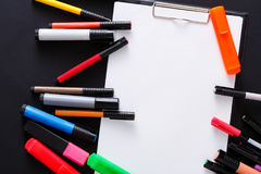 Stationery for drawing, markers and blank paper. Stationery for drawing - top view of color markers variety and tablet with white blank paper on black desktop Royalty Free Stock Photos