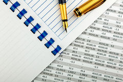 Stationery and financial document. Gold metal ink pen, notebook and classic financial document royalty free stock photo