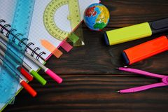 Stationery with a globe and markers spread out on a notebook lying on a dark wooden table, top viewn royalty free stock photography