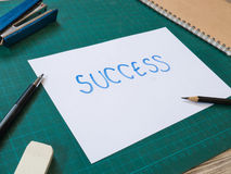Stationery and hand writing success text paper on cutting mat Stock Photos