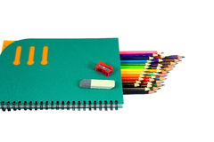 Stationery. Lie on a white background notebook, sharpener, eraser and lots of colored pencils Stock Photo