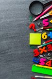 Stationery and math exercises. Assorted school supplies and simple math exercises lying on surface of clean blackboard