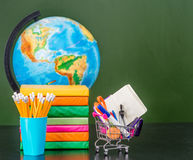 Stationery near empty green chalkboard Royalty Free Stock Images