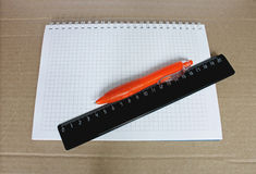 Stationery. Notebook, orange pen and a black line on a coarse brown paper background Royalty Free Stock Images