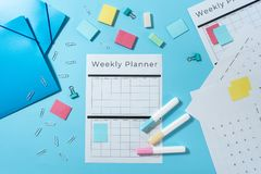 Stationery and planner on blue pastel background. Top view of folders, colorful stationery and weekly planner with copy space on pastel blue background stock images