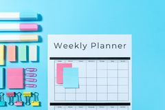 Stationery and planner on blue pastel background. Top view of weekly planner, colorful sticky notes, stationery, marker and paperclip on pastel blue background stock images