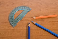 Stationery products, a protractor and some colored pencils on a. Wood table composition stock photo