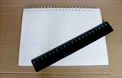 Stationery. A ruler and a notebook in the box on the rough brown paper background Stock Images