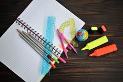 Stationery scattered on a notebook lying on a dark wooden table, stock image