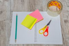 Stationery: scissors, tape, pen, pencil and notebook on a wooden table stock photography
