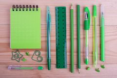 Stationery set in green color. Bright school chancery on wooden table. Office stationery for study stock photography
