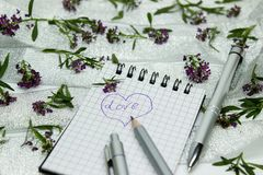 Stationery on small purple flowers and silver ribbon Stock Photography