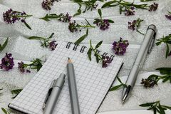 Stationery on small purple flowers and silver ribbon Stock Images