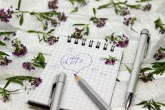 Stationery on small purple flowers and silver ribbon Stock Photo