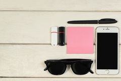 Stationery, sunglasses, telephone, flash memory cards on a wooden table Stock Photos