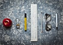 Stationery tools for the education of engineering students. Workspace on a concrete background. I have an idea!. Ruler, marker, pencil, pen, glasses, apple stock photos