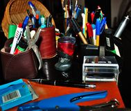 Stationery varies pens, pencils, erasers, stamps all piled up.  stock photos