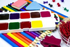 Watercolor paints, pencils of different colors, plasticine and erasers, buttons and paper clips isolated on a white background