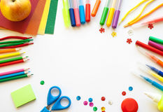 Stationery on the white background. Multicolor pencils and crayons, apple and multi-colored sequins. Place for your text Royalty Free Stock Photography